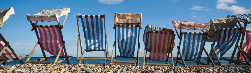 colourful striped deck chairs on a pebbled beach;  ... United Kingdom